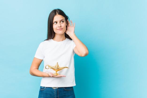 Jeune femme caucasienne tenant une lampe magique essayant d'écouter un potin.
