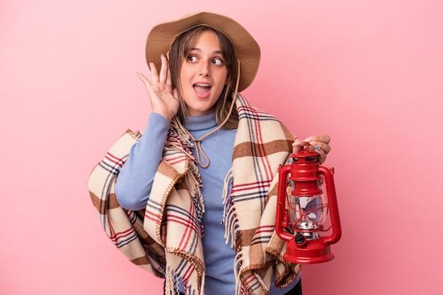 Jeune femme caucasienne tenant une lanterne vintage isolée sur fond rose essayant d'écouter un potin.