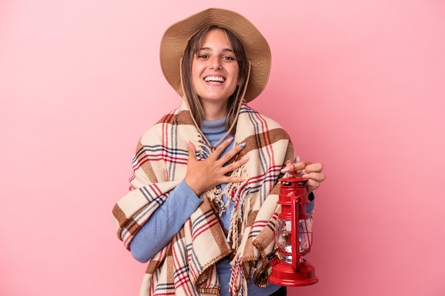 Jeune femme caucasienne tenant une lanterne vintage isolée sur fond rose rit fort en gardant la main sur la poitrine.