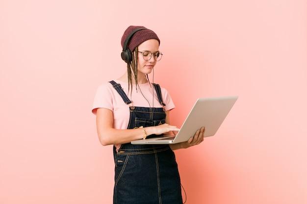 Jeune femme caucasienne tenant un ordinateur portable souriant confiant avec les bras croisés.