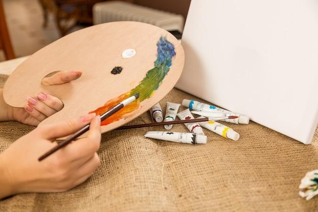 Jeune femme caucasienne tenant une palette en bois avec des peintures