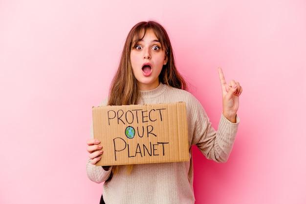 Jeune femme caucasienne tenant une pancarte protéger notre planète isolée ayant une idée, un concept d'inspiration.