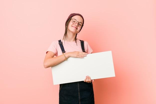 Jeune femme caucasienne tenant une pancarte souriant confiant avec les bras croisés.