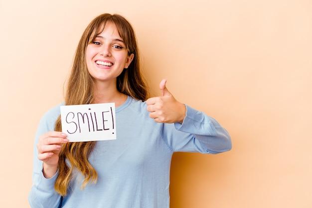 Jeune femme caucasienne tenant une pancarte de sourire souriant et levant le pouce vers le haut