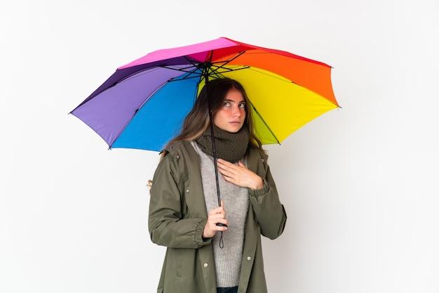 Jeune femme caucasienne tenant un parapluie isolé sur fond blanc ayant des doutes et de la pensée