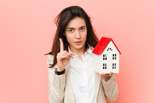 Jeune femme caucasienne tenant une petite maison