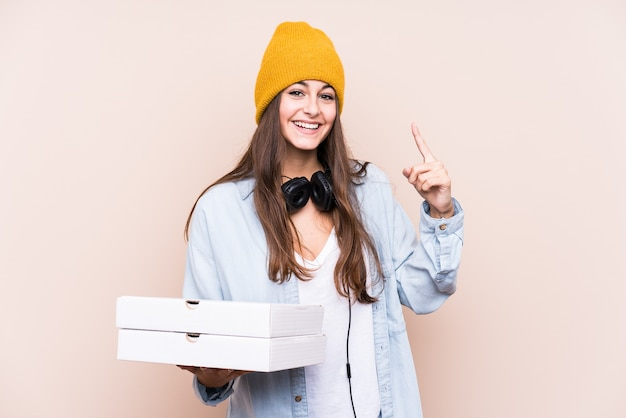 Jeune femme caucasienne tenant des pizzas isolées ayant une idée, un concept d'inspiration.
