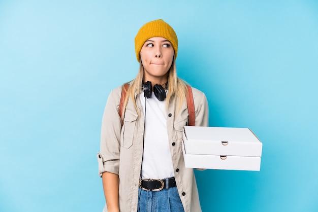Jeune femme caucasienne tenant des pizzas isolées confus, se sent douteux et incertain.