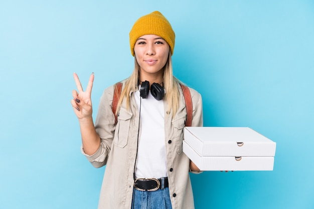 Jeune femme caucasienne tenant des pizzas isolées montrant le numéro deux avec les doigts.