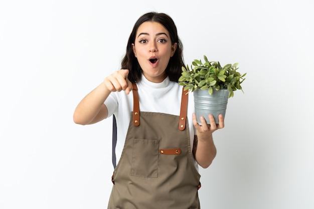 Jeune femme caucasienne tenant une plante isolée