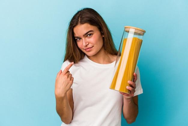 Jeune femme caucasienne tenant un pot de pâtes isolé sur fond bleu pointant du doigt vers vous comme si vous vous invitiez à vous rapprocher.