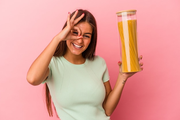 Jeune femme caucasienne tenant un pot de pâtes isolé sur fond rose excité en gardant le geste ok sur les yeux.