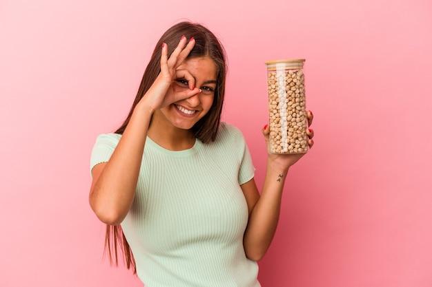 Jeune femme caucasienne tenant un pot de pois chiches isolé sur fond rose excité en gardant le geste ok sur les yeux.