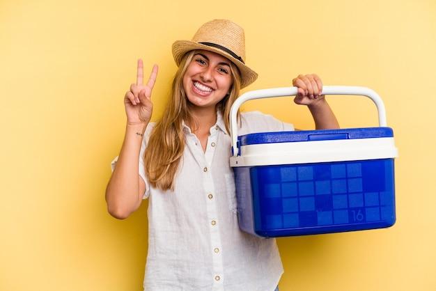 Jeune femme caucasienne tenant un réfrigérateur isolé sur fond jaune montrant le numéro deux avec les doigts.