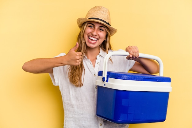 Jeune femme caucasienne tenant un réfrigérateur isolé sur fond jaune souriant et levant le pouce vers le haut