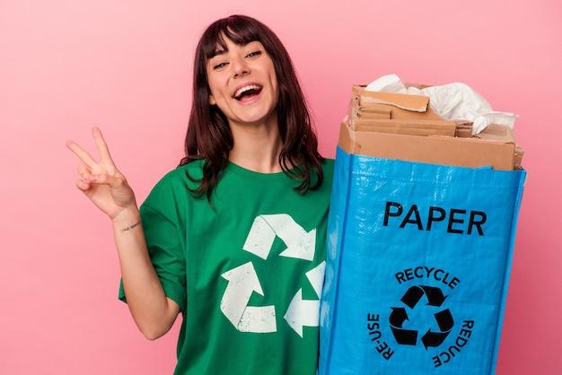 Jeune femme caucasienne tenant un sac en carton recyclé isolé sur fond rose joyeux et insouciant montrant un symbole de paix avec les doigts.