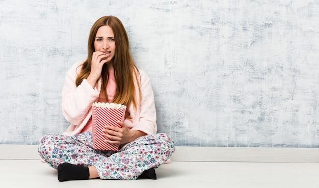 Jeune femme caucasienne tenant un seau de pop-corn se ronger les ongles, nerveux et très anxieux.