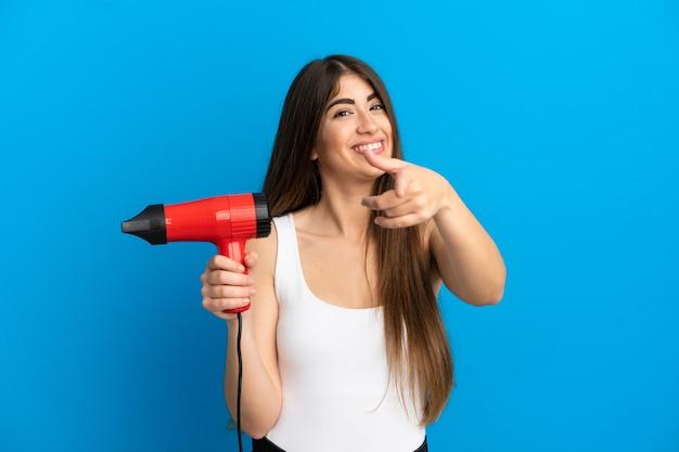 Jeune femme caucasienne tenant un sèche-cheveux isolé sur fond bleu pointant vers l'avant avec une expression heureuse