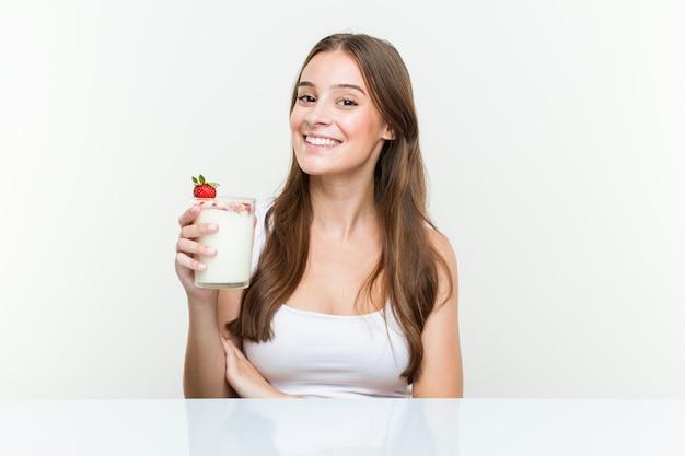 Jeune femme caucasienne tenant un smoothie souriant confiant avec les bras croisés.