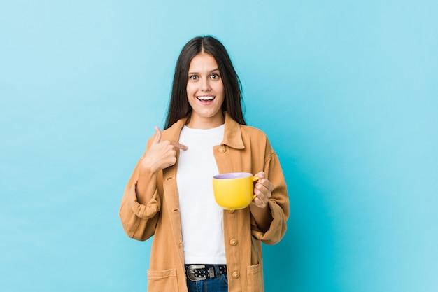 Jeune femme caucasienne tenant une tasse de café surprise, pointant le doigt vers lui-même, souriant largement.