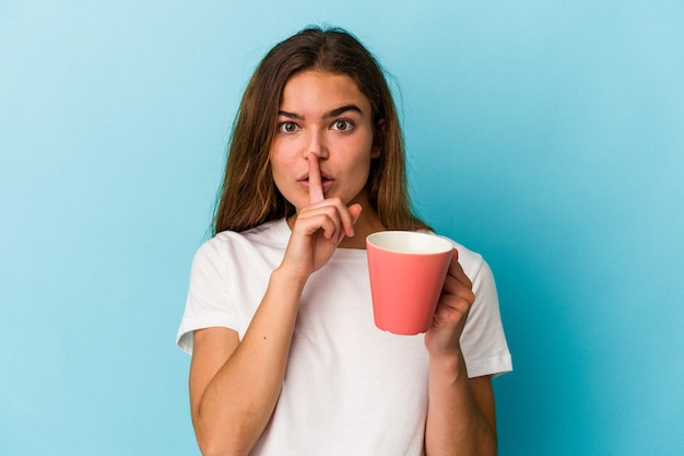 Jeune femme caucasienne tenant une tasse isolée sur fond bleu gardant un secret ou demandant le silence.