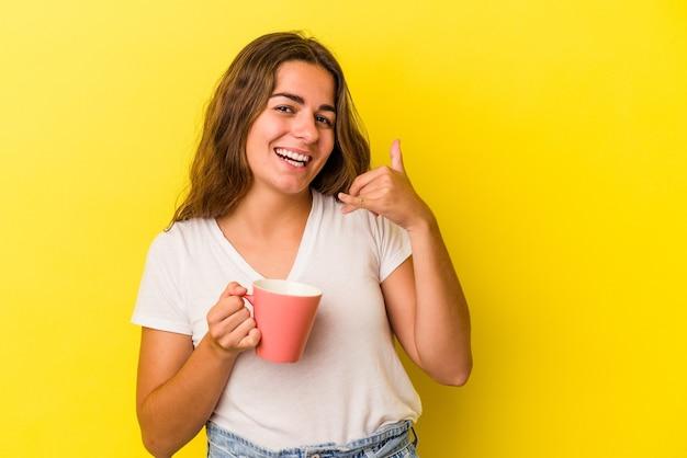 Jeune femme caucasienne tenant une tasse isolée sur fond jaune montrant un geste d'appel de téléphone portable avec les doigts.