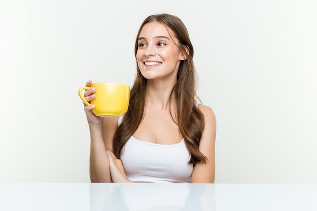 Jeune femme caucasienne tenant une tasse souriante confiante avec les bras croisés.