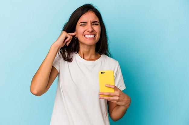 Jeune femme caucasienne tenant un téléphone portable isolé sur fond bleu couvrant les oreilles avec les mains.