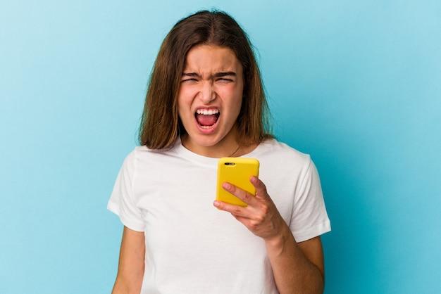 Jeune femme caucasienne tenant un téléphone portable isolé sur fond bleu criant très en colère et agressive.