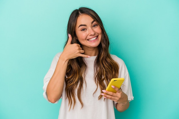 Jeune femme caucasienne tenant un téléphone portable isolé sur fond bleu montrant un geste d'appel de téléphone portable avec les doigts.