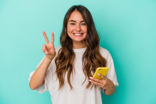 Jeune femme caucasienne tenant un téléphone portable isolé sur fond bleu montrant le numéro deux avec les doigts.