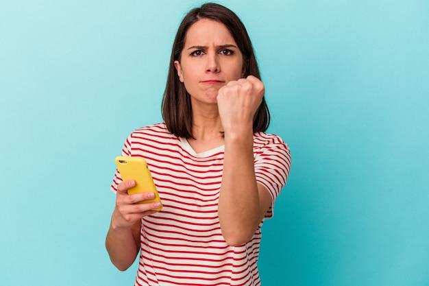 Jeune femme caucasienne tenant un téléphone portable isolé sur fond bleu montrant le poing à la caméra, expression faciale agressive.