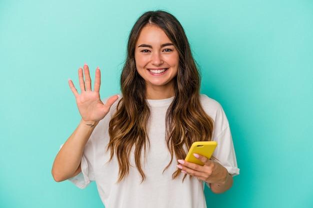 Jeune femme caucasienne tenant un téléphone portable isolé sur fond bleu souriant joyeux montrant le numéro cinq avec les doigts.