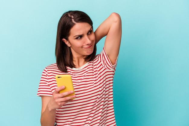Jeune femme caucasienne tenant un téléphone portable isolé sur fond bleu touchant l'arrière de la tête, pensant et faisant un choix.