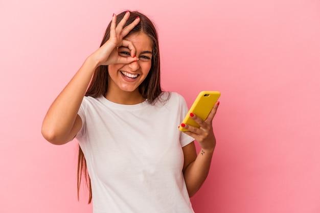 Jeune femme caucasienne tenant un téléphone portable isolé sur fond rose excité en gardant le geste ok sur les yeux.