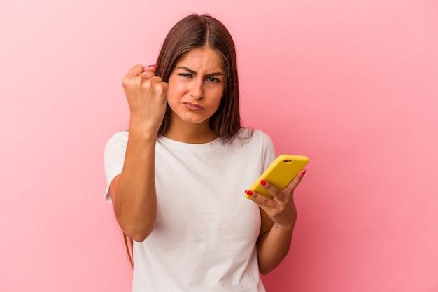 Jeune femme caucasienne tenant un téléphone portable isolé sur fond rose montrant le poing à la caméra, expression faciale agressive.