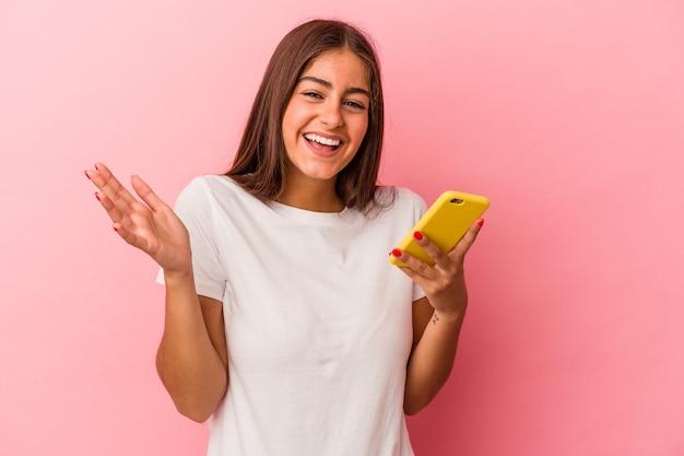 Jeune femme caucasienne tenant un téléphone portable isolé sur fond rose recevant une agréable surprise, excitée et levant les mains.