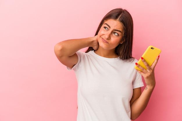 Jeune femme caucasienne tenant un téléphone portable isolé sur fond rose touchant l'arrière de la tête, pensant et faisant un choix.
