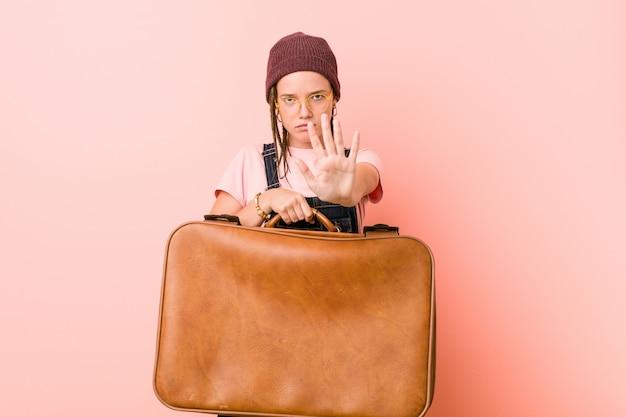 Jeune femme caucasienne tenant une valise debout avec la main tendue montrant le panneau d'arrêt, vous empêchant.