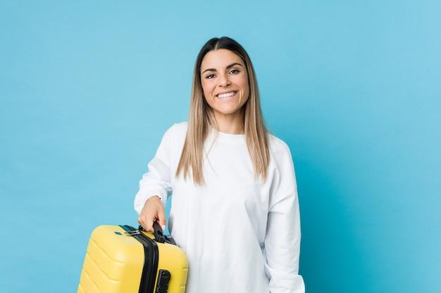 Jeune femme caucasienne tenant une valise heureuse, souriante et joyeuse.