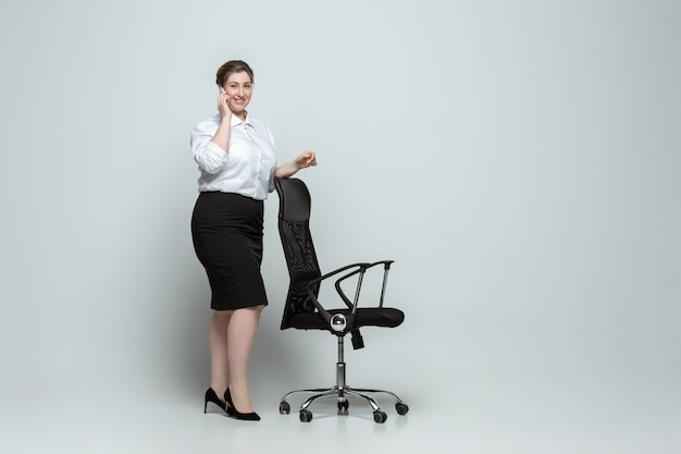 Jeune femme caucasienne en tenue de bureau sur mur gris