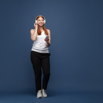 Jeune femme caucasienne en tenue décontractée, écoutant de la musique