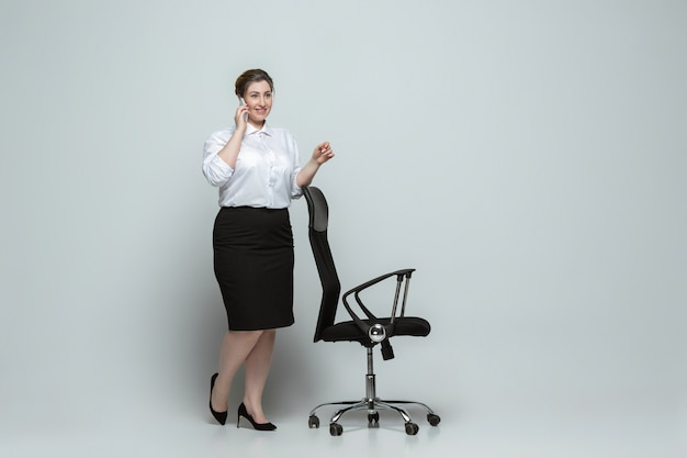 Jeune femme caucasienne en tenue décontractée sur gris. personnage féminin bodypositive, plus la taille