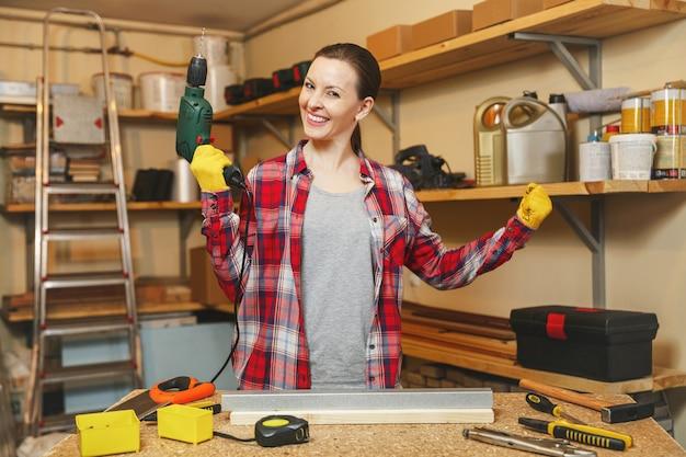 Jeune femme caucasienne très amusante aux cheveux bruns en chemise à carreaux et t-shirt gris travaillant dans un atelier de menuiserie à table, perçant des trous dans un morceau de fer et de bois tout en fabriquant des meubles.