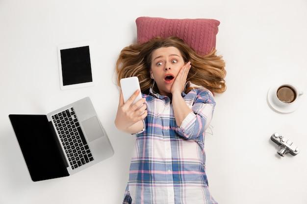 Jeune femme caucasienne utilisant des appareils, des gadgets isolés sur le mur blanc du studio.