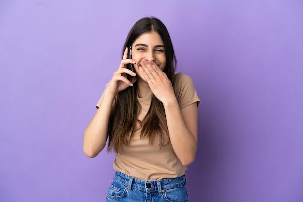 Jeune femme caucasienne utilisant un téléphone portable isolé sur fond violet heureux et souriant couvrant la bouche avec la main