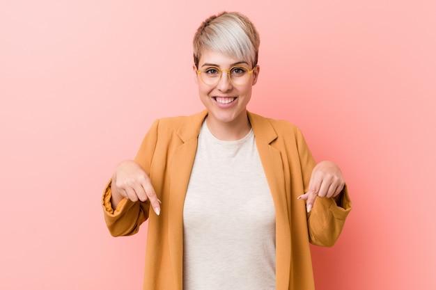 Jeune femme caucasienne vêtue d'une tenue de travail décontractée pointe vers le bas avec les doigts, sentiment positif.