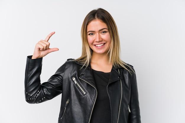 Jeune femme caucasienne vêtue d'une veste en cuir noir tenant quelque chose de peu avec l'index, souriant et confiant.