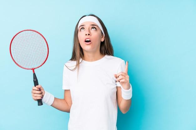 Jeune femme caucasique jouant au badminton isolé pointant vers le haut avec la bouche ouverte.