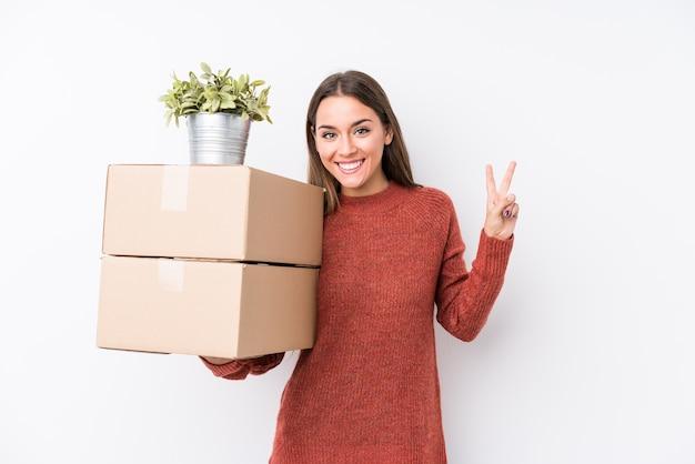 Jeune femme caucasique tenant des boîtes isolées joyeuses et insouciantes montrant un symbole de paix avec les doigts.